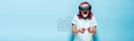 Photo for KYIV, UKRAINE - JULY 29, 2020: excited young woman with pink hair in vr headset playing video game with joystick on blue background, panoramic shot - Royalty Free Image