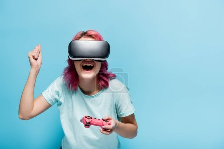 Photo for KYIV, UKRAINE - JULY 29, 2020: excited young woman with pink hair in vr headset with joystick on blue background - Royalty Free Image