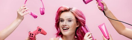 Photo for KYIV, UKRAINE - JULY 29, 2020: young woman with colorful hair near straightener, headphones, cosmetic cream, joystick and hairdryer in hands isolated on pink, panoramic shot - Royalty Free Image