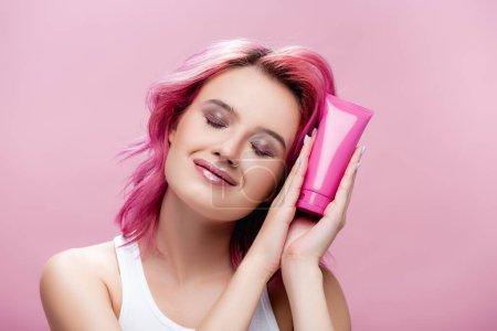 mujer joven con el pelo colorido y los ojos cerrados sosteniendo tubo de crema cosmética aislado en rosa