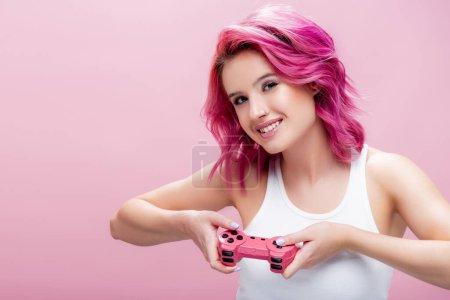 Photo pour KYIV, UKRAINE - 29 JUILLET 2020 : jeune femme aux cheveux colorés tenant joystick isolé sur rose - image libre de droit