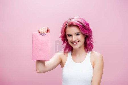 Photo for Young woman with colorful hair presenting book isolated on pink - Royalty Free Image