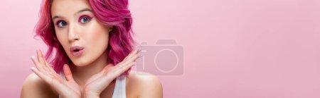 mujer joven sorprendida con el pelo colorido y maquillaje posando con las manos cerca de la cara aislado en rosa, tiro panorámico