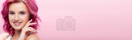 Photo for Young woman with colorful hair and makeup posing with hand near face isolated on pink, panoramic shot - Royalty Free Image