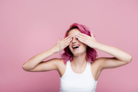 young woman with colorful hair smiling and covering eyes with hands isolated on pink