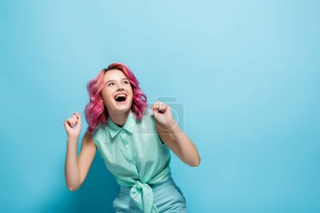 young woman with pink hair rejoicing on blue background