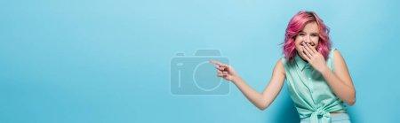 Photo pour Jeune femme aux cheveux roses pointant du doigt et riant sur fond bleu, plan panoramique - image libre de droit