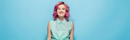 Photo pour Jeune femme aux cheveux roses souriant sur fond bleu, plan panoramique - image libre de droit