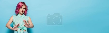 Photo for Confused young woman with pink hair showing refusal on blue background, panoramic shot - Royalty Free Image