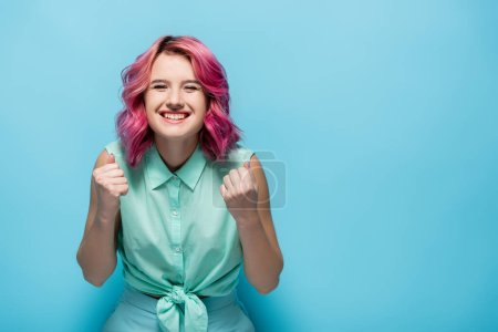 Photo for Young woman with pink hair showing yeah gesture on blue background - Royalty Free Image