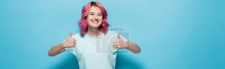 young woman with pink hair showing thumbs up on blue background, panoramic shot