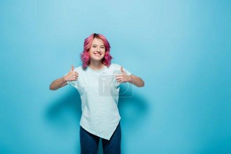 Photo pour Jeune femme aux cheveux roses montrant les pouces vers le haut sur fond bleu - image libre de droit