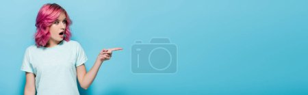 Photo for Surprised young woman with pink hair pointing aside on blue background, panoramic shot - Royalty Free Image