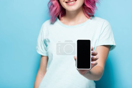 cropped view of young woman with pink hair holding smartphone with blank screen on blue background