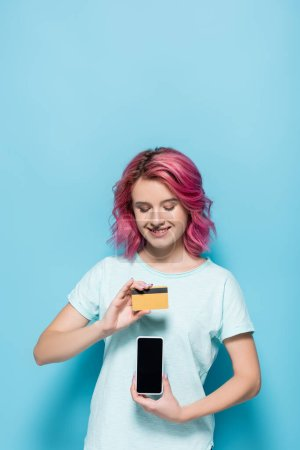 Photo for Young woman with pink hair holding credit card and smartphone on blue background - Royalty Free Image