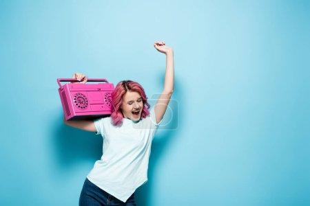 Photo pour Excité jeune femme avec les cheveux roses tenant magnétophone vintage et la danse sur fond bleu - image libre de droit