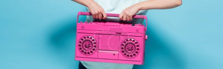 cropped view of young woman holding vintage tape recorder on blue background, panoramic shot