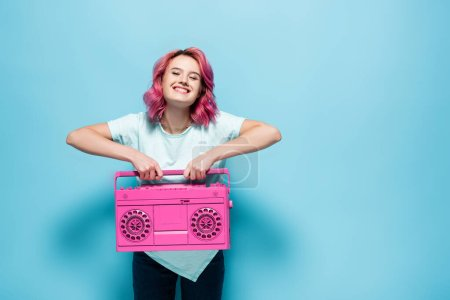Photo for Young woman with pink hair holding vintage tape recorder on blue background - Royalty Free Image