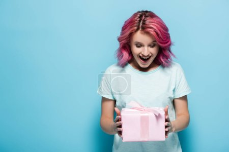 Photo pour Excité jeune femme avec des cheveux roses tenant boîte cadeau avec arc sur fond bleu - image libre de droit