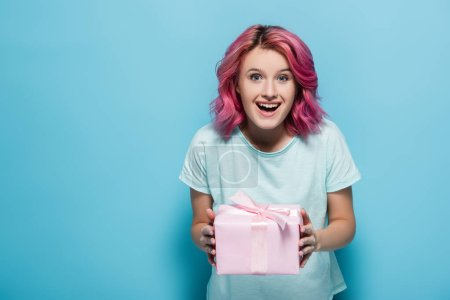 excited young woman with pink hair holding gift box with bow on blue background