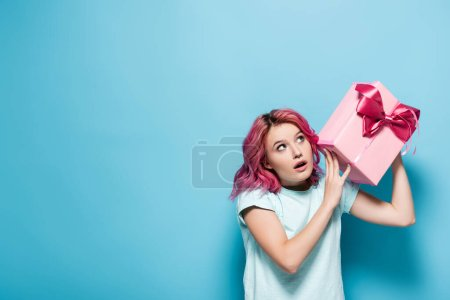 young woman with pink hair and open mouth holding gift box with bow on blue background