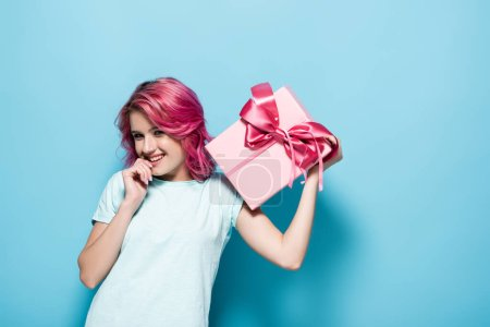 young woman with pink hair holding gift box with bow and smiling on blue background