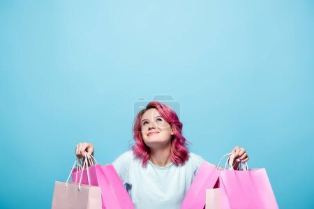 Photo for Young woman with pink hair holding shopping bags and looking up on blue background - Royalty Free Image