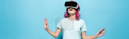 shocked young woman with pink hair in vr headset gesturing on blue background, panoramic shot