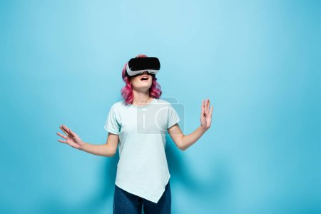 Photo for Shocked young woman with pink hair in vr headset gesturing on blue background - Royalty Free Image