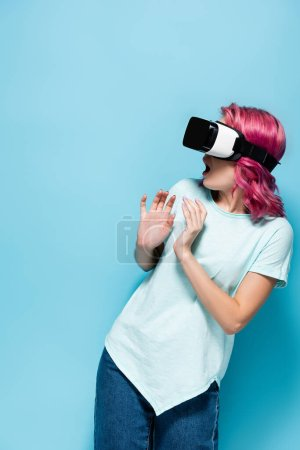 scared young woman with pink hair in vr headset on blue background
