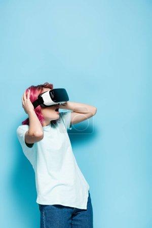 Photo pour Choqué jeune femme avec des cheveux roses en vr casque tenant la tête sur fond bleu - image libre de droit
