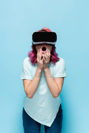 shocked young woman with pink hair in vr headset touching face on blue background