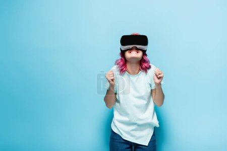 excited young woman with pink hair in vr headset showing yeah gesture on blue background
