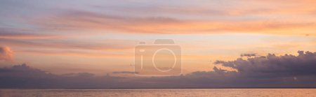 Panoramic shot of sea and cloudy sky at sunset