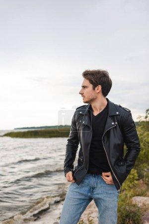 Photo pour Jeune homme en jean et veste en cuir regardant la côte de la mer - image libre de droit