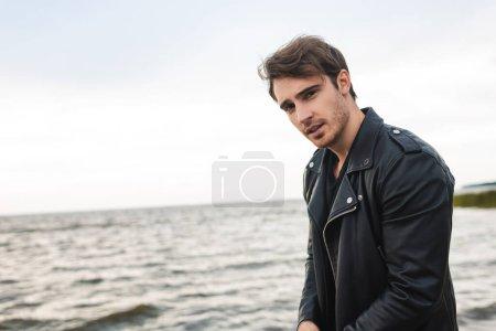 Photo pour Jeune homme en veste en cuir regardant la caméra près de la mer - image libre de droit