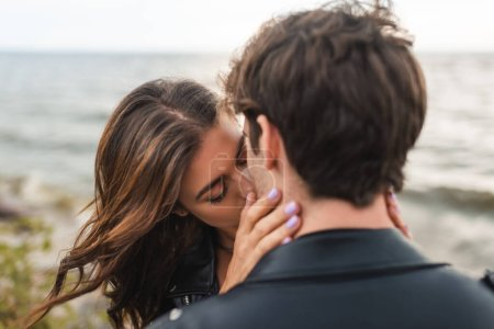 Photo pour Concentration sélective de la jeune femme embrasser petit ami sur la côte de la mer - image libre de droit