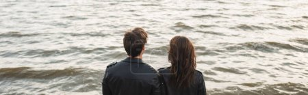 Photo for Horizontal crop of young couple in leather jackets standing near sea - Royalty Free Image