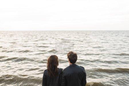 Photo pour Vue arrière du couple en vestes en cuir noir regardant la mer - image libre de droit