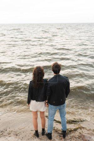 Photo pour Vue arrière de l'homme en veste en cuir debout près de petite amie sur la plage près de la mer - image libre de droit