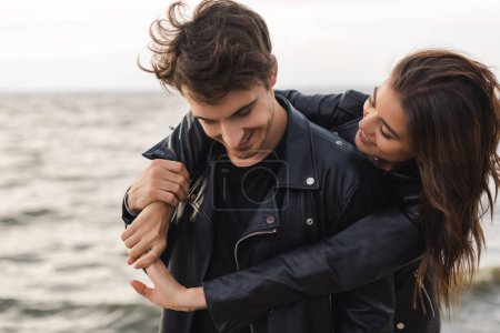 Photo pour Brunette femme câlin petit ami en cuir veste près de la mer - image libre de droit