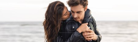 Photo pour Plan panoramique d'une jeune femme embrassant son petit ami en veste de cuir au bord de la mer - image libre de droit