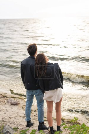 Photo for Back view of young couple standing on sandy beach near sea - Royalty Free Image