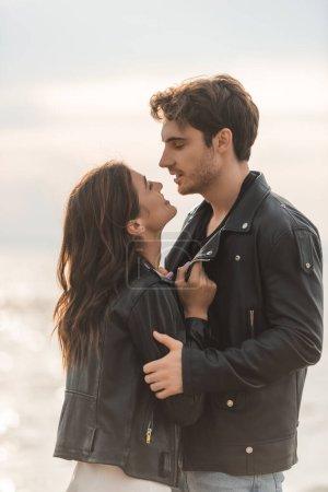 Photo pour Jeune femme touchant veste en cuir de petit ami près de la mer - image libre de droit