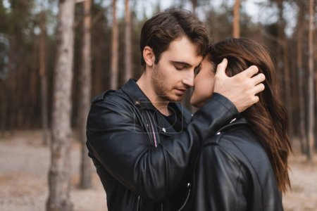 Photo for Man in leather jacket kissing and touching girlfriend in forest - Royalty Free Image