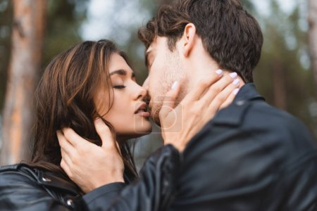 Selective focus of young couple in leather jackets kissing in forest