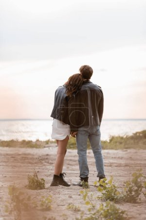 Photo for Back view of couple in leather jackets standing on sea beach at sunset - Royalty Free Image
