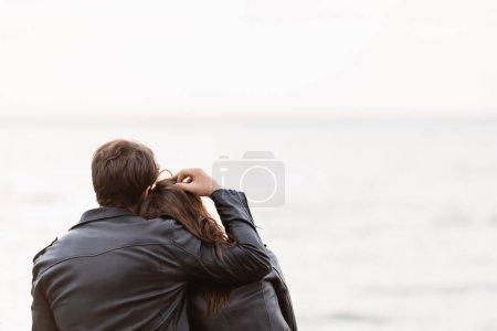 Photo pour Vue arrière de l'homme en veste en cuir toucher les cheveux de la petite amie près de la mer - image libre de droit
