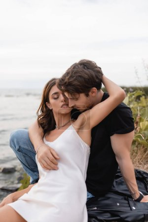 Photo for Woman in dress hugging boyfriend on leather jacket on beach - Royalty Free Image