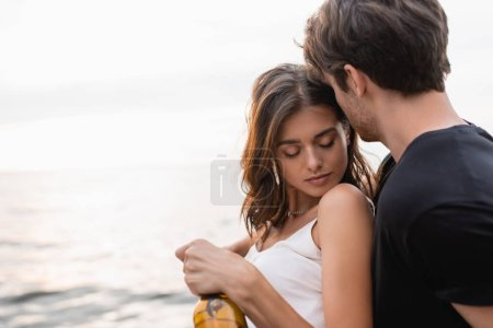 Photo for Young man holding bottle of wine and hugging brunette girlfriend near sea - Royalty Free Image